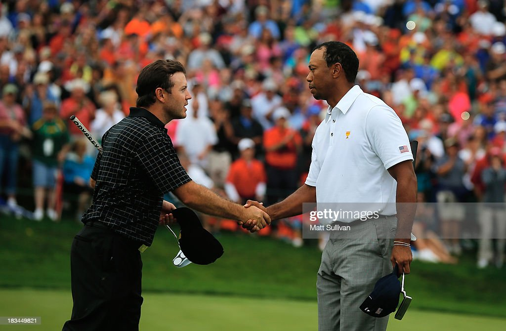 <a gi-track='captionPersonalityLinkClicked' href=/galleries/search?phrase=Tiger+Woods&family=editorial&specificpeople=157537 ng-click='$event.stopPropagation()'>Tiger Woods</a> of the U.S. Team (R) shakes hands with <a gi-track='captionPersonalityLinkClicked' href=/galleries/search?phrase=Richard+Sterne&family=editorial&specificpeople=243113 ng-click='$event.stopPropagation()'>Richard Sterne</a> of South Africa and the International Team on the 18th green after Woods 1up victory won the Cup for the U.S.Team during the Day Four Singles Matches at the Muirfield Village Golf Club on October 6, 2013 in Dublin, Ohio.