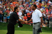 Tiger Woods of the US Team shakes hands with Richard Sterne of South Africa and the International Team on the 18th green after Woods 1up victory won...