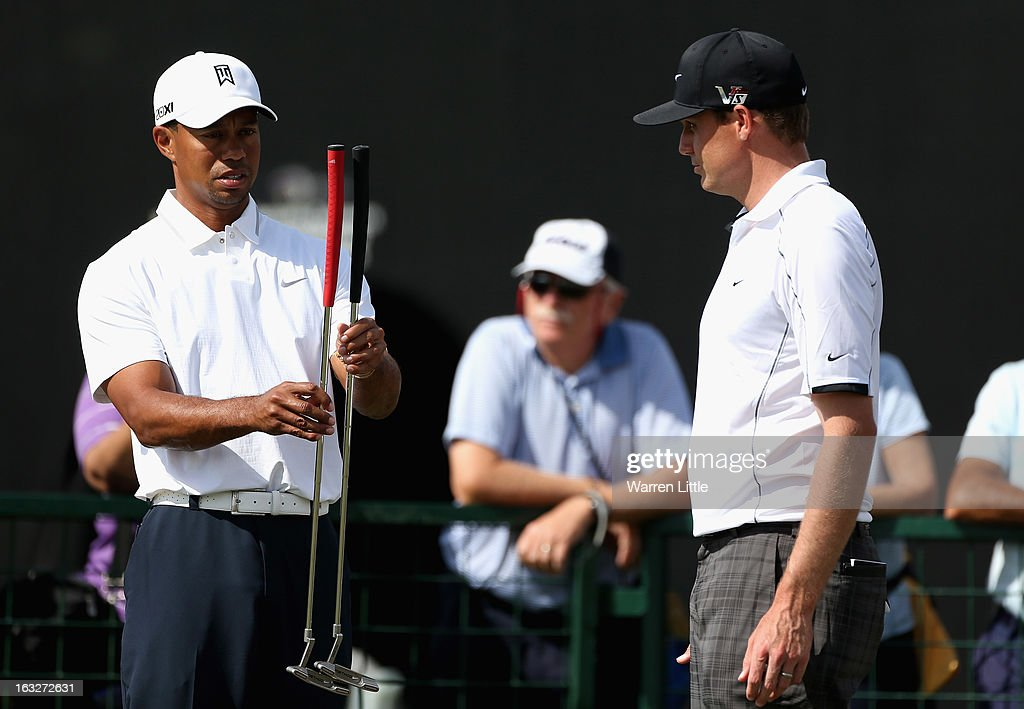 Tiger Woods of the USA compares putters with Nick Watney of the USA on the practice putting green ahead of the WGC - Cadillac Championship at the Doral Golf Resort & Spa on March 6, 2013 in Miami, Florida.