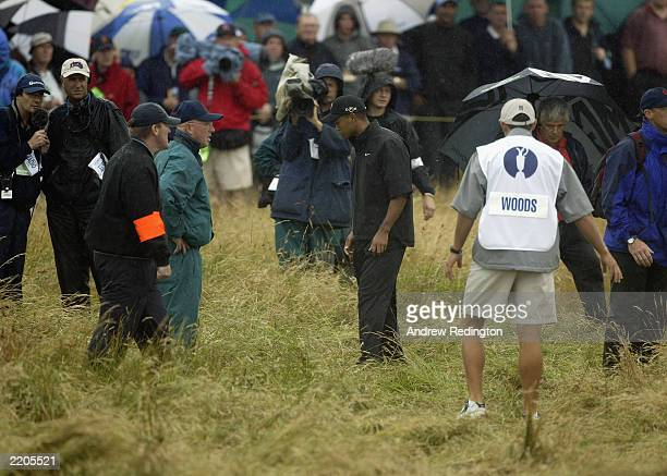 Tiger Woods of the USA looks for his ball together with marshalls on the first fairway during the first round of The Open Championship at the Royal...
