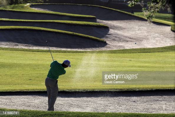 Tiger Woods of the USA plays from a fairway bunker against the early morning sun during the proam as a preview for the 2012 Arnold Palmer...