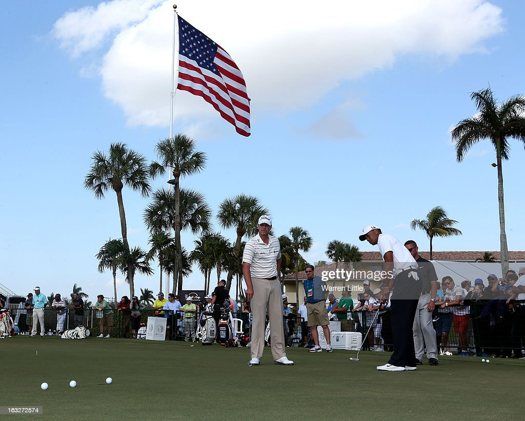 Tiger Woods of the USA putts with Steve Stricker of the USA on the practice putting green ahead of the WGC - Cadillac Championship at the Doral Golf Resort & Spa on March 6, 2013 in Miami, Florida.
