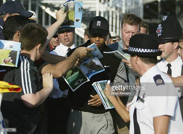 Tiger Woods of the USA signs autographs after his practice round for the 132nd Open Championship at the Prince's Golf Club on July 13 2003 in...