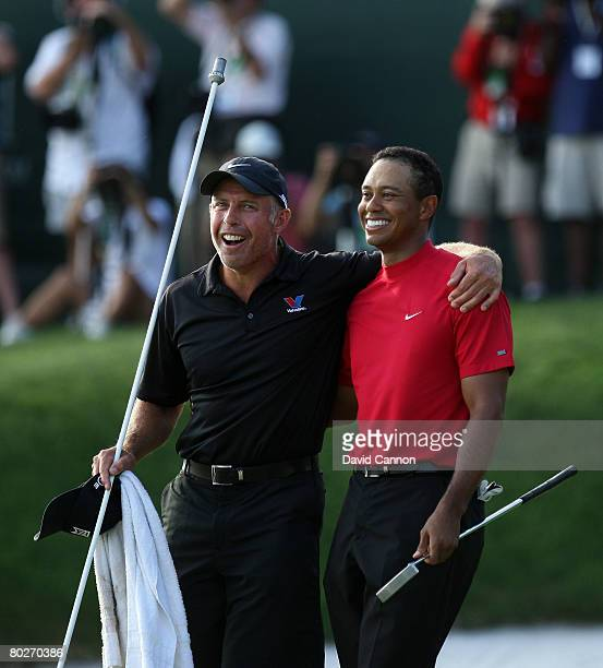 Tiger Woods of the USA stands with his caddie Steve Williams of New Zealand after holing his winning birdie putt at the 18th hole during the final...