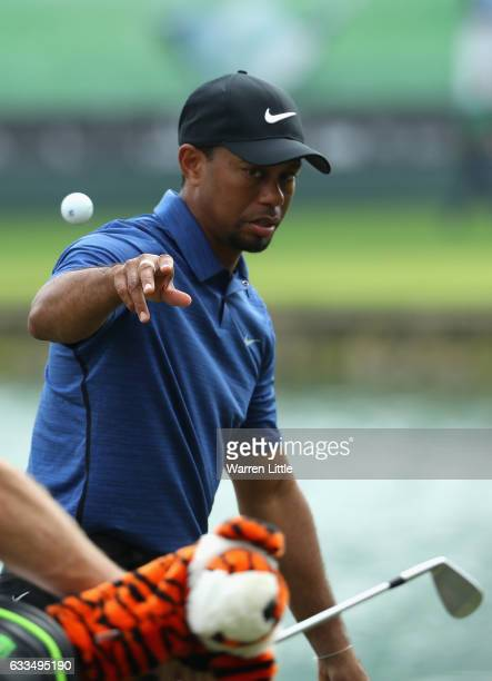 Tiger Woods of the USA throws his ball to caddie Joe LaCava during the first round of the Omega Dubai Desert Classic at Emirates Golf Club on...