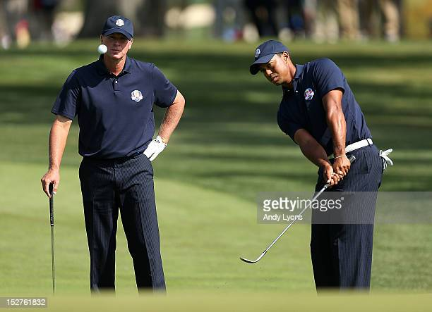 Tiger Woods of the USA watches a pitch shot as Steve Stricker looks on during a practice round during the second preview day of The 39th Ryder Cup at...