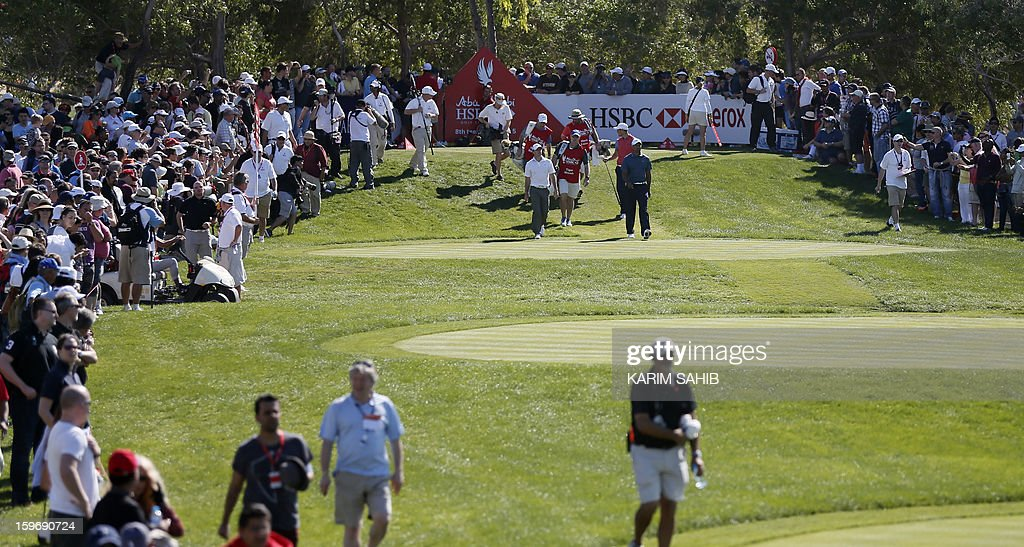 Tiger Woods of US and Rory McIlroy (L) of Northern Ireland walk during the second round of the Abu Dhabi Golf Championship at the Abu Dhabi Golf Club in the Emirati capital on January 18, 2013.
