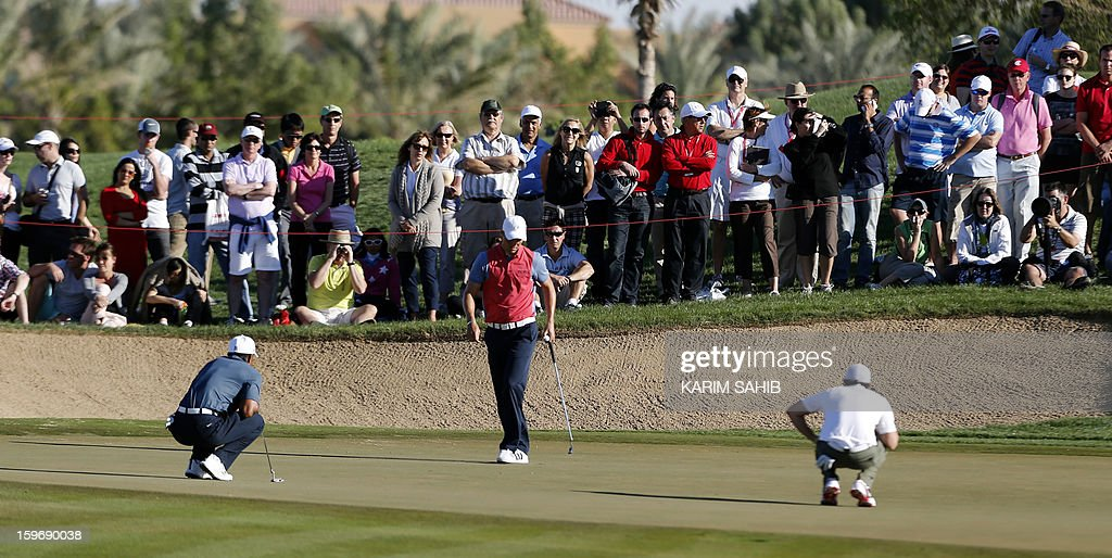 Tiger Woods of US, Martin Kaymer of Germany (C) and Rory McIlroy (R) of Northern Ireland line up a putt during the second round of the Abu Dhabi Golf Championship at the Abu Dhabi Golf Club in the Emirati capital on January 18, 2013.