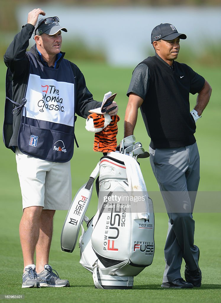Tiger Woods of USA and caddie Joe LaCava ponder during the third round of the Honda Classic on March 2, 2013 in Palm Beach Gardens, Florida.