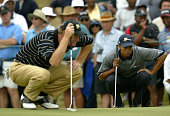 Tiger Woods of USA and Ernie Els of South Africa line up putts during the first round of fourballs at The Presidents Cup between USA and The...