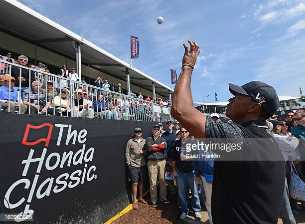Tiger Woods of USA catches his ball after he putt his second shot into the grandstand on the 18th hole during the third round of the Honda Classic on...