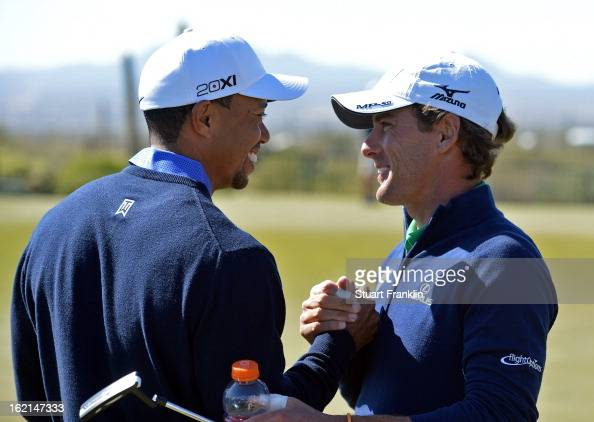 Tiger Woods of USA greets his apponant of the first day Charles Howell III of USA during practice prior to the start of the World Golf...