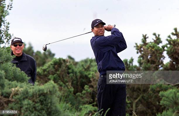 Tiger Woods of USA tees off on the 10th among the evergreens while his trainer Butch Harmon watches on the Old Course at St Andrews during his...