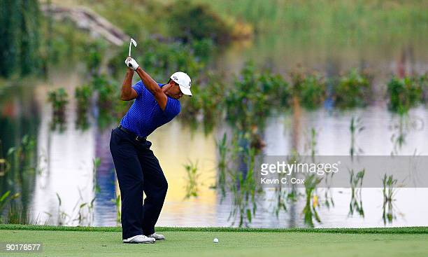 Tiger Woods plays his fourth shot in the 13th fairway after a drop during round three of The Barclays on August 29 2009 at Liberty National in Jersey...