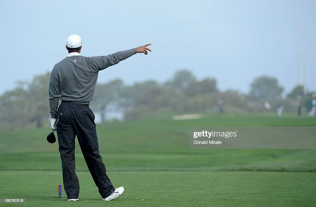 Tiger Woods points to where he wants his ball to turn after hitting off the tee box during the Third Round at the Farmers Insurance Open at Torrey Pines South Golf Course on January 27, 2013 in La Jolla, California.