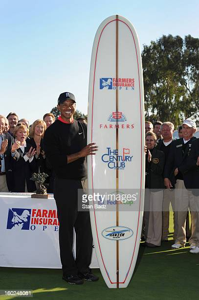 Tiger Woods poses with a surfboard celebrating his win at the Farmers Insurance Open at Torrey Pines Golf Course on January 28 2013 in La Jolla...