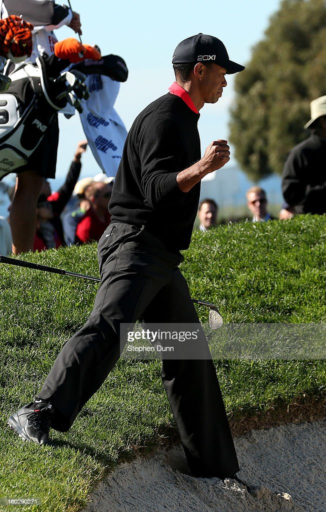 Tiger Woods pumps his fist after hitting an awkward lie out of a bunker on the 11th hole during the final round of the Farmers Insurance Open on the South Course at Torrey Pines Golf Course on January 28, 2013 in La Jolla, California.