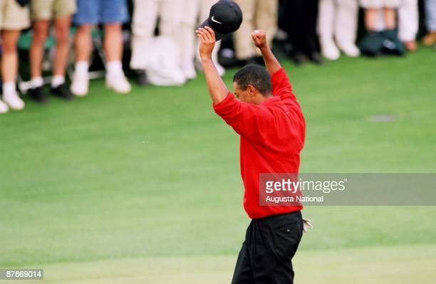 Tiger Woods raises his arms in victory on the 18th hole after winning the 1997 Masters Tournament at Augusta National Golf Club on April 13 1997 in...