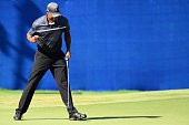 Tiger Woods reacts after making an eagle putt on the 15th green during the second round of the Wyndham Championship at Sedgefield Country Club on...