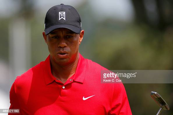 Tiger Woods reacts after making his par putt on the first hole during the final round of the Wyndham Championship at Sedgefield Country Club on...