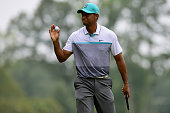 Tiger Woods reacts after scoring a birdie on the 1st hole during the first round of the Wyndham Championship at Sedgefield Country Club on August 20...