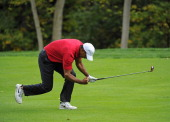 Tiger Woods reacts to his second shot from the 15th fairway during the Day Three Fourball Matches of The Presidents Cup at Muirfield Village Golf...