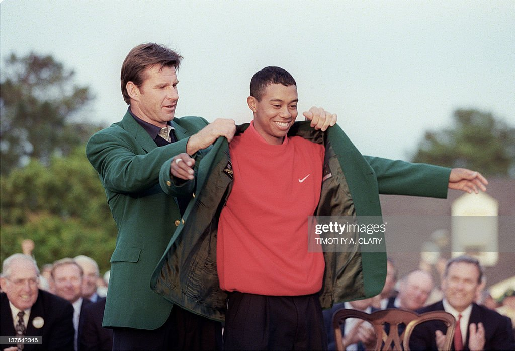 Tiger Woods receives the Masters green jacket from 1996 Masters champion Nick Faldo after Woods won the 1997 Masters tournament 13 April 1997 at...