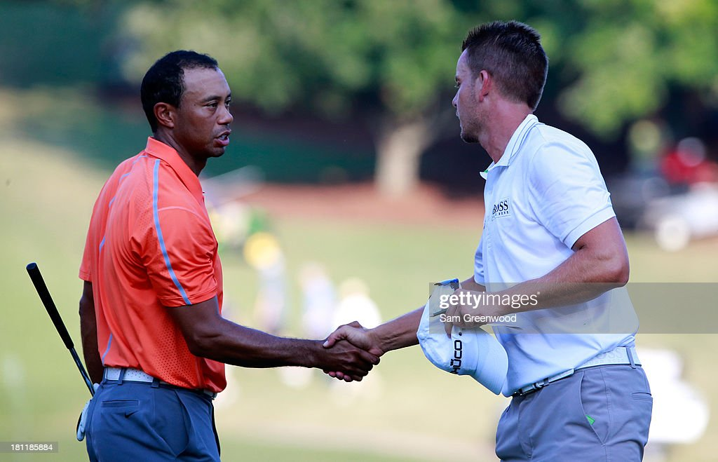 Tiger Woods (L) shakes hands with Henrik Stenson of Sweden following the first round of the TOUR Championship by Coca-Cola at East Lake Golf Club on September 19, 2013 in Atlanta, Georgia.
