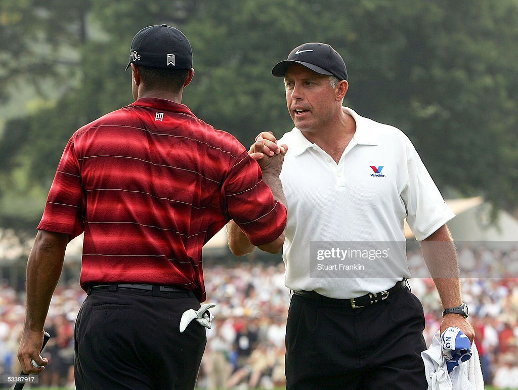 Tiger Woods (L) shakes hands with his caddie, Steve Williams, on the 18th green after shooting a two-under par 68 during the final round of the 2005 PGA Championship on August 14, 2005 at Baltusrol Golf Club in Springfield, New Jersey.