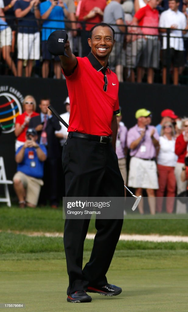 Tiger Woods smiles and points to the crowd on the 18th green after the Final Round of the World Golf Championships-Bridgestone Invitational at Firestone Country Club South Course on August 4, 2013 in Akron, Ohio. Woods won the tournament with a score of -15.