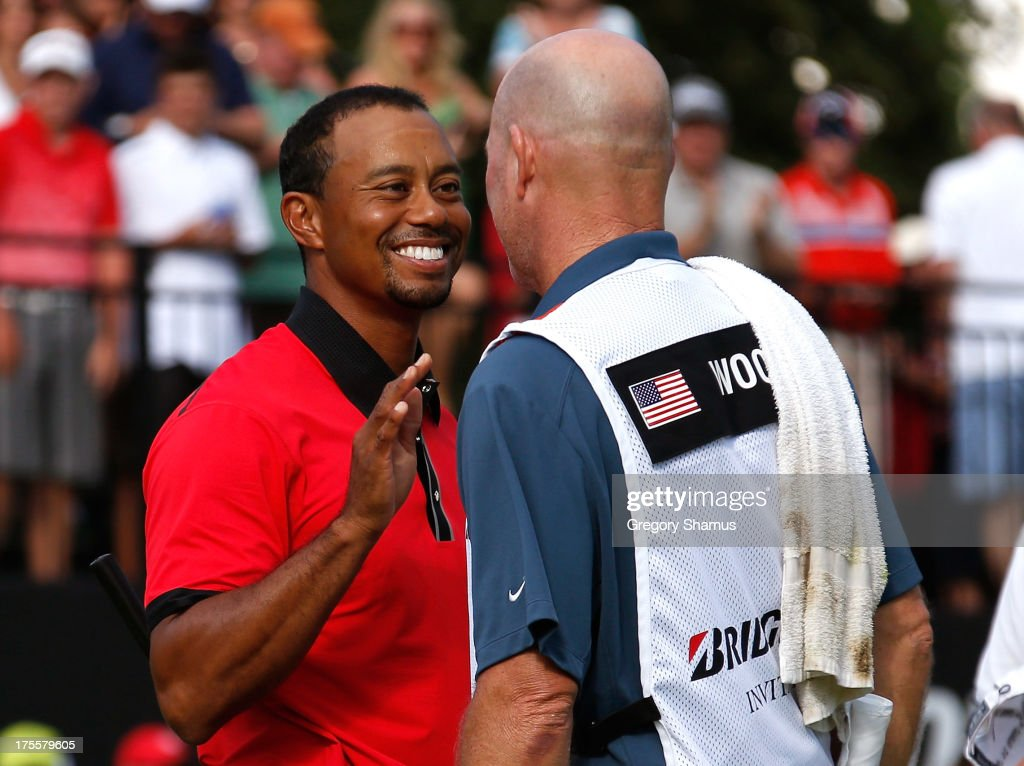Tiger Woods (L) smiles and speaks with caddie Joe LaCava after the Final Round of the World Golf Championships-Bridgestone Invitational at Firestone Country Club South Course on August 4, 2013 in Akron, Ohio. Woods won the tournament with a score of -15.