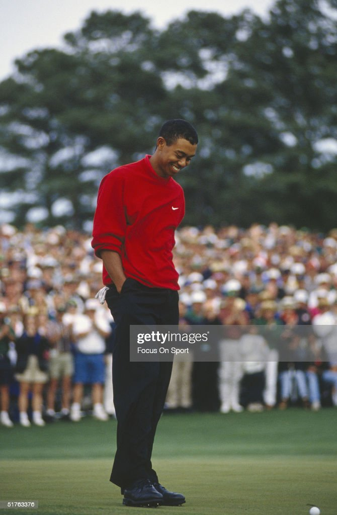 Tiger Woods smiles at his ball on the green during the Masters Tournament at the Augusta National Golf Club on April 13, 1997 in Augusta, Georgia. Tiger Woods won the Masters with a 18 under par.