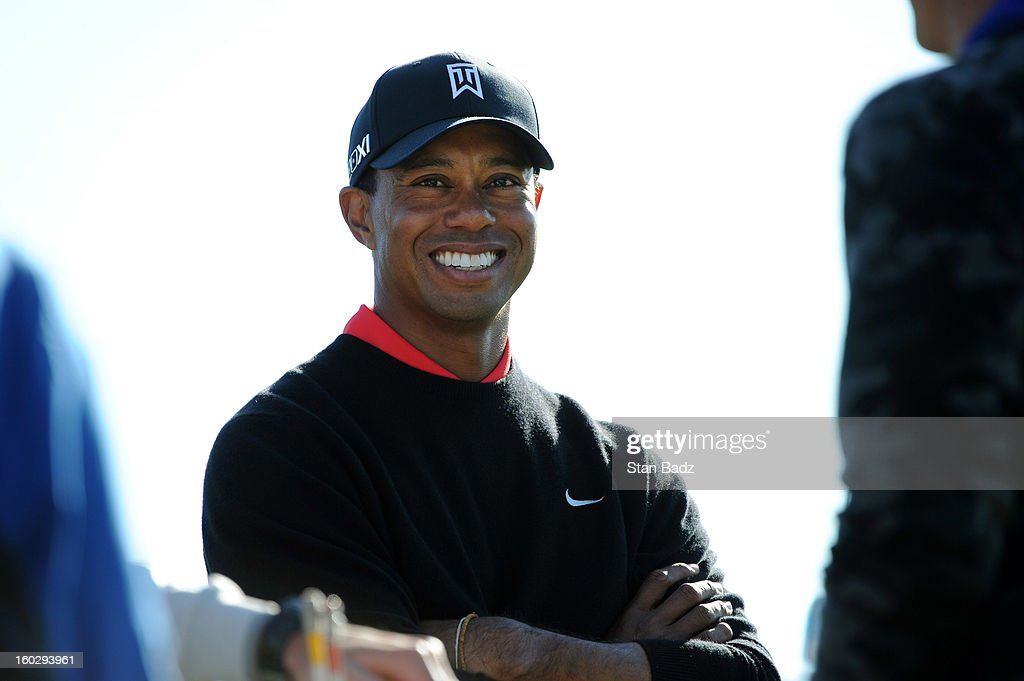 Tiger Woods smilies as he waits to play the 18th hole during the final round of the Farmers Insurance Open at Torrey Pines Golf Course on January 28, 2013 in La Jolla, California.
