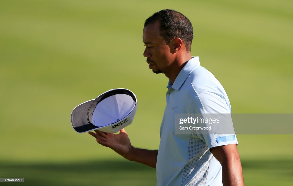Tiger Woods spins his hat after finishing the 18th hole during the Third Round of the World Golf Championships-Bridgestone Invitational at Firestone Country Club South Course on August 3, 2013 in Akron, Ohio.