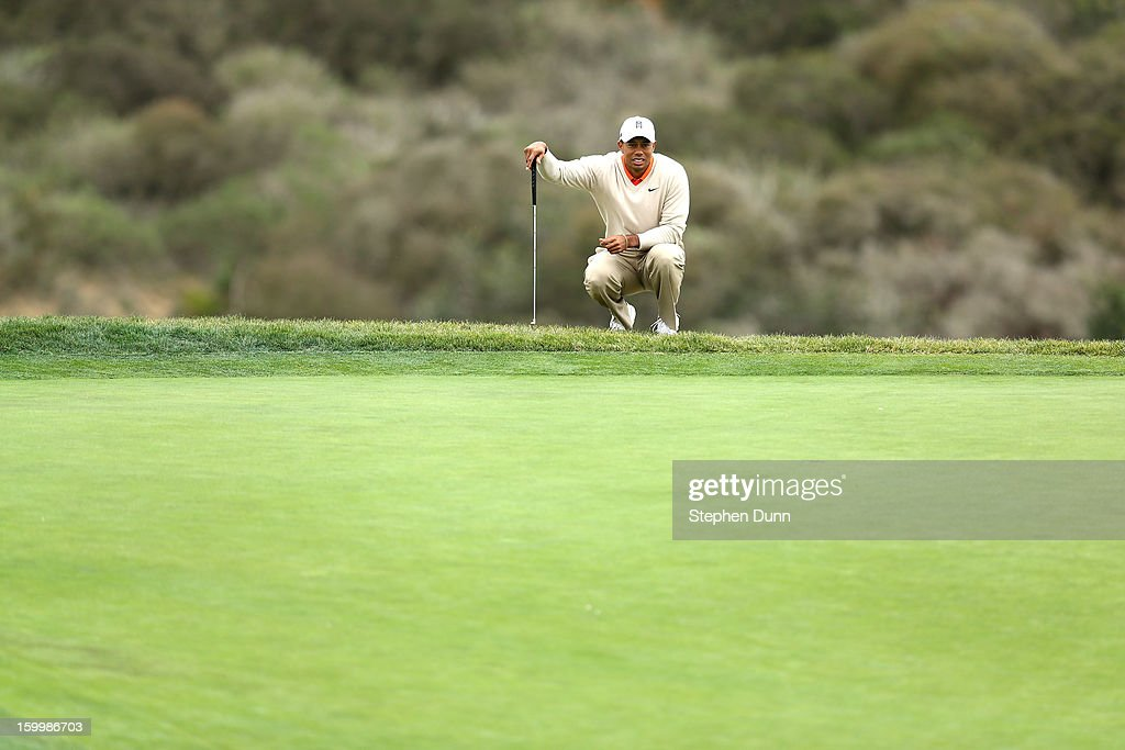 Tiger Woods studies the green on the third hole during the first round of the Farmers Insurance Open on the South Course at Torrey Pines Golf Course on January 24, 2013 in La Jolla, California.