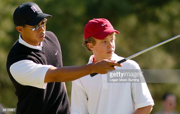 Tiger Woods teaches twelveyearold Ty Boley during his Junior Clinic April 16 2004 at Fort Bragg North Carolina After spending the week training with...