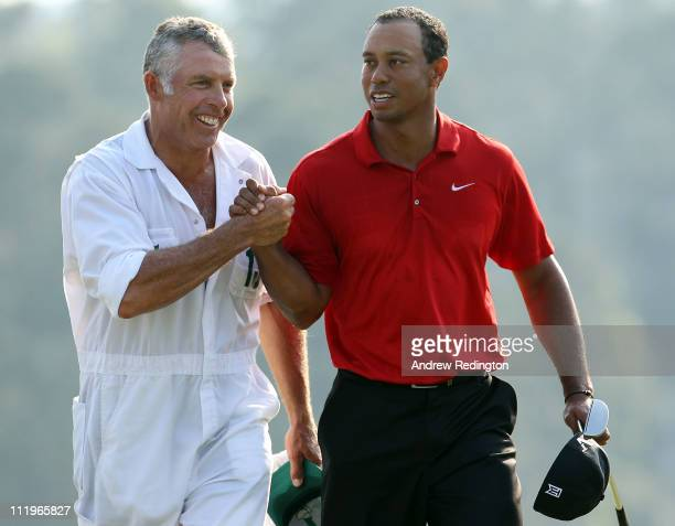 Tiger Woods walks off the 18th green with his caddie Steve Williams during the final round of the 2011 Masters Tournament at Augusta National Golf...