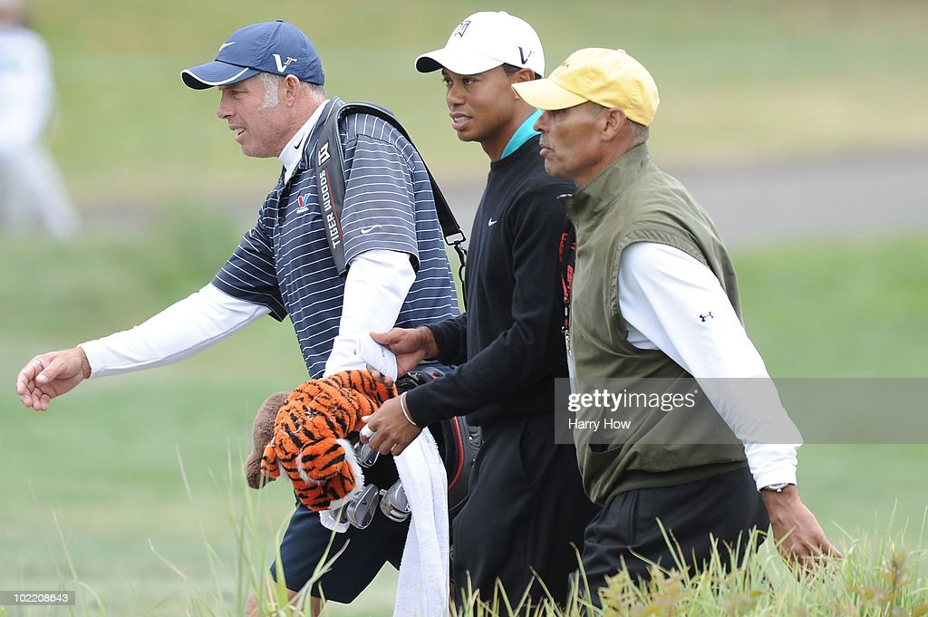 Tiger Woods walks off the ninth green alongside his caddie Steve Williams and fomer NFL head coach Herman Edwards during the second round of the...