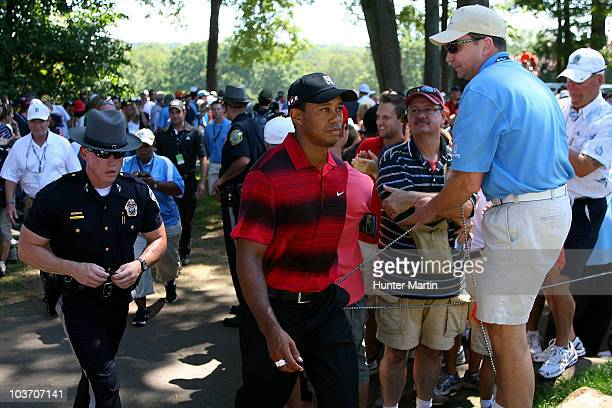 Tiger Woods walks through the gallery of fans between the fifth green and the tee box on the sixth hole during the final round of The Barclays at the...