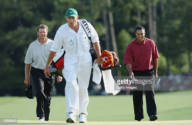 Tiger Woods walks up the 18th hole with Retief Goosen of South Africa during the final round of the Masters at Augusta National Golf Club in Augusta...