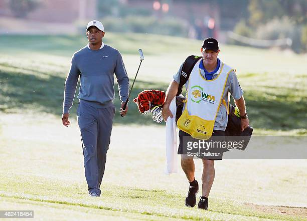 Tiger Woods walks with his caddie Joe LaCava to a green during the proam prior to the start of the Waste Management Phoenix Open at TPC Scottsdale on...