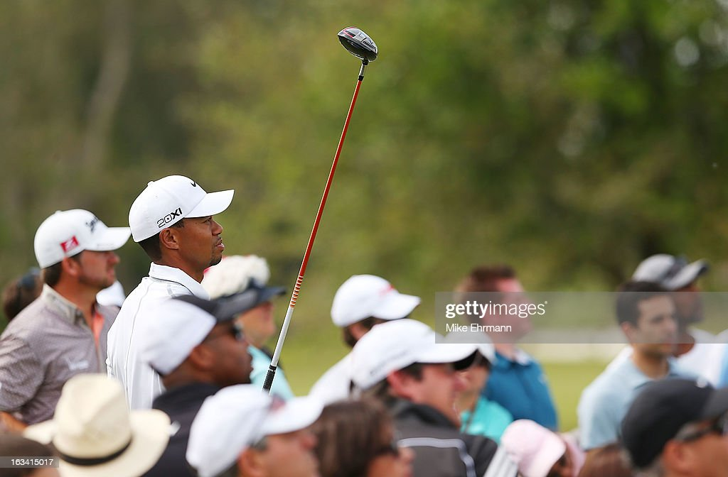 Tiger Woods watches his tee shot on the third hole as Graeme McDowell of Northern Ireland looks on during the third round of the World Golf Championships-Cadillac Championship at the Trump Doral Golf Resort & Spa on March 9, 2013 in Doral, Florida.