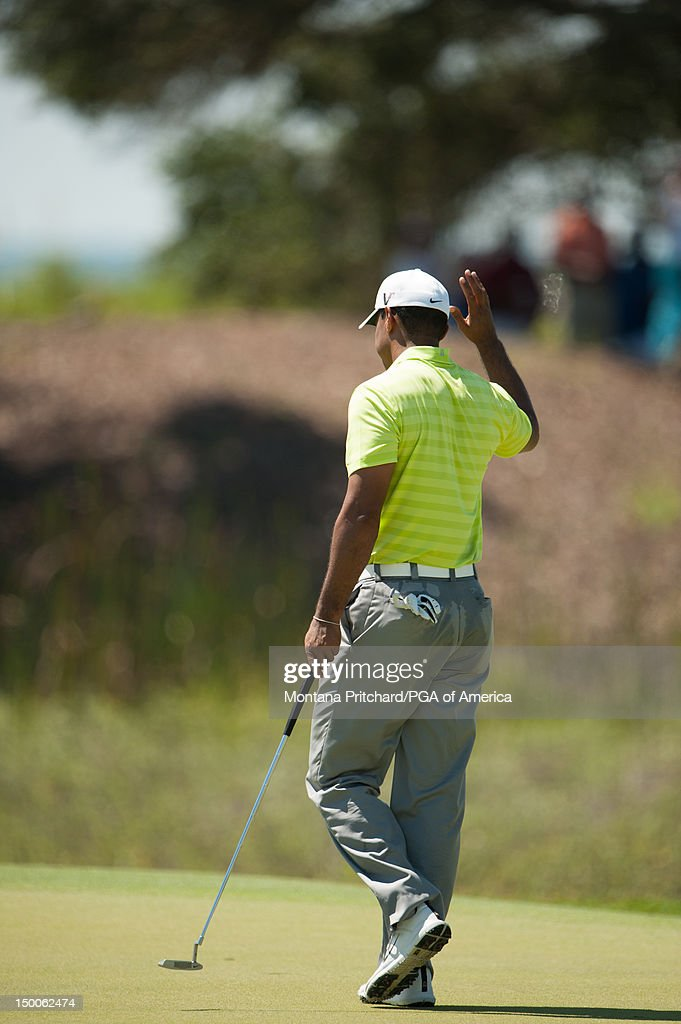 Tiger Woods waves after making a birdie putt on the second during the first round for the 94th PGA Championship at The Ocean Course at Kiawah Island Resort on August 9, 2012 in Kiawah Island, South Carolina.