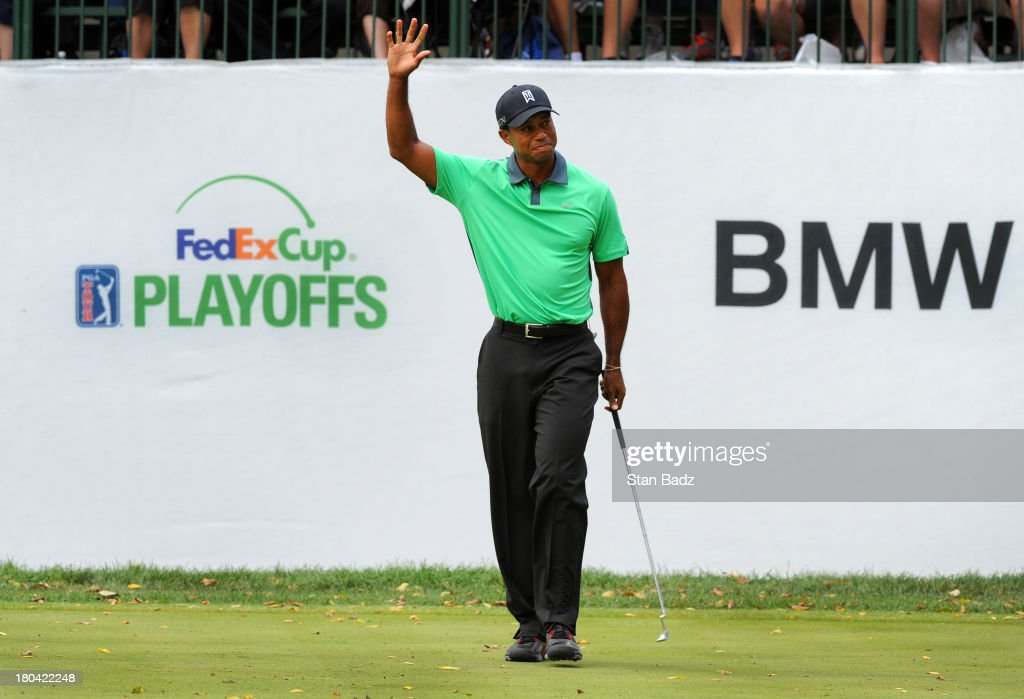 Tiger Woods waves as the crowd reacts to his birdie on the ninth hole during the first round of the BMW Championship at Conway Farms Golf Club on September 12, 2013 in Lake Forest, Illinois.