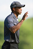 Tiger Woods waves to the crowd after making a par putt on the 17th green during the second round of the Wyndham Championship at Sedgefield Country...