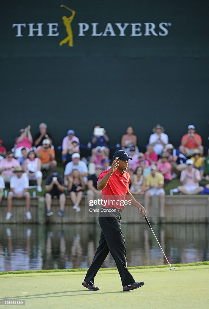 Tiger Woods waves to the gallery on the 18th green during the final round of THE PLAYERS Championship on THE PLAYERS Stadium Course at TPC Sawgrass on May 12, 2013 in Ponte Vedra Beach, Florida.
