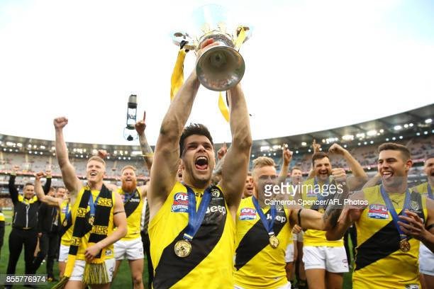 Tigers captain Trent Cotchin celebrates with team mates and holds the AFL Premiership Cup aloft after winning the 2017 AFL Grand Final match between...