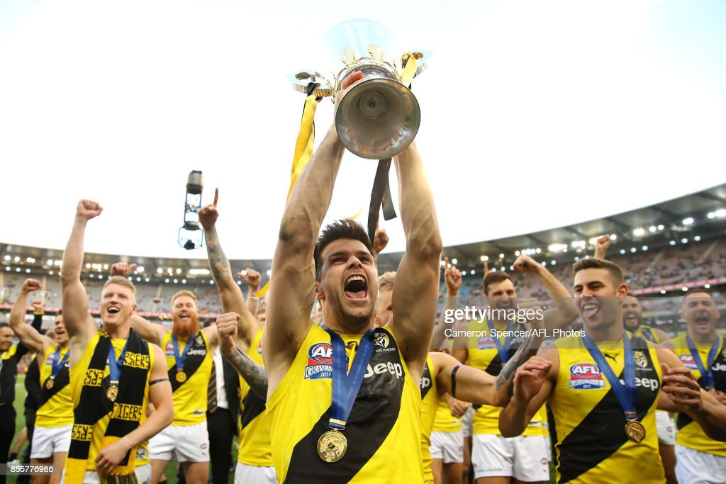 Tigers captain Trent Cotchin celebrates with team mates and holds the AFL Premiership Cup aloft after winning the 2017 AFL Grand Final match between the Adelaide Crows and the Richmond Tigers at Melbourne Cricket Ground on September 30, 2017 in Melbourne, Australia.