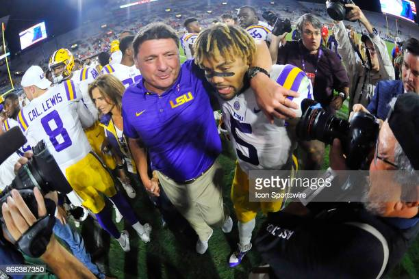 Tigers coach Ed Orgeron puts his arms around running back Derrius Guice after winning a NCAA college football game against the Mississippi Rebels on...