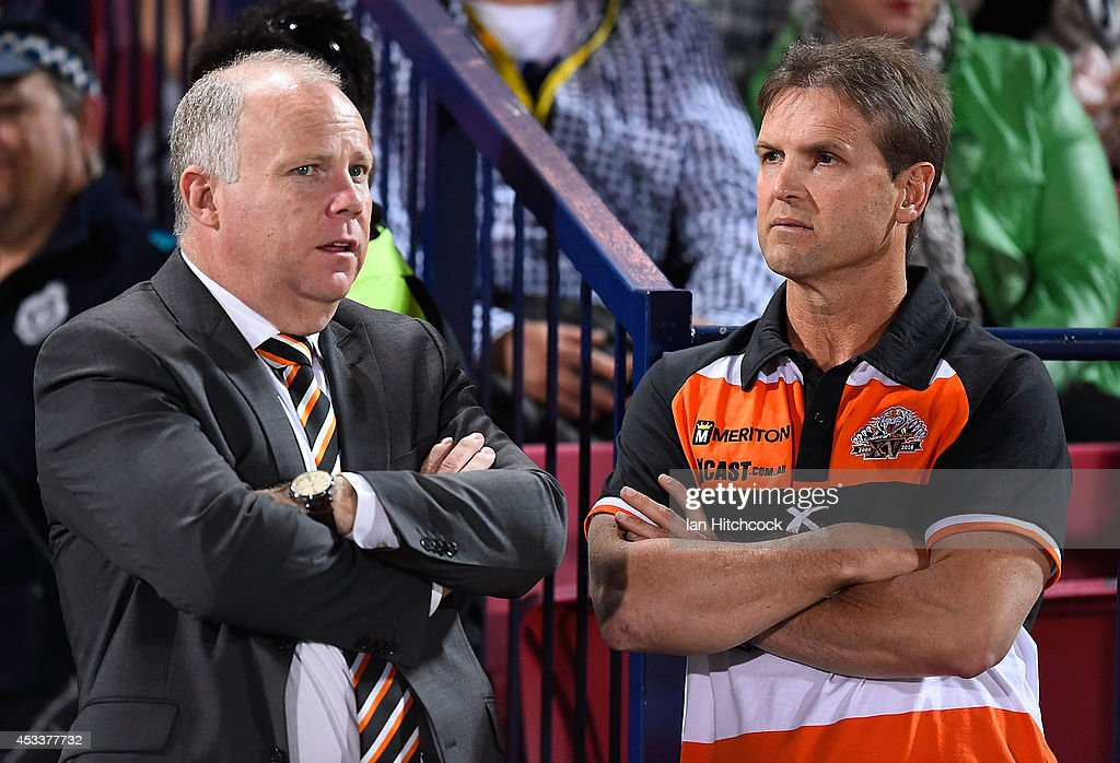 Tigers coach Mick Potter talks with Tigers CEO Grant Mayer before the start of the round 22 NRL match between the North Queensland Cowboys and the Wests Tigers at 1300SMILES Stadium on August 9, 2014 in Townsville, Australia.